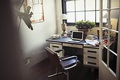 Laptop and paperwork on desk in home office