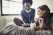 Women with headphones and coffee using digital tablet on bed