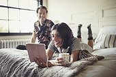 Smiling couple relaxing, drinking coffee and using digital tablet on bed