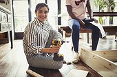 Portrait smiling woman with power drill assembling furniture