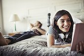 Smiling young woman with headphones using digital tablet on bed