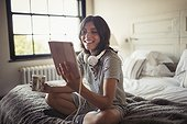 Smiling young woman with headphones drinking coffee and using digital tablet on bed
