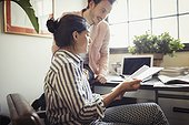 Businessman and businesswoman reviewing and discussing paperwork in office