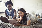Smiling women drinking coffee and using digital tablet on bed