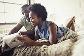 Couple relaxing, reading newspaper on bed