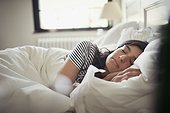 Tired, serene young woman sleeping in bed