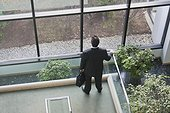Businessman with briefcase in atrium of office building