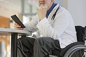 Doctor with muscular dystrophy in wheelchair looking at his tablet