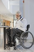Doctor with muscular dystrophy in wheelchair talking on smartphone