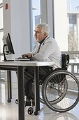 Doctor with muscular dystrophy in wheelchair studying information on his computer
