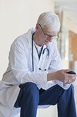 Doctor reading a text message on mobile phone
