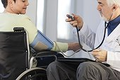 Doctor with muscular dystrophy in wheelchair checking the blood pressure of a patient