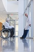 Doctor with muscular dystrophy in wheelchair talking with another doctor