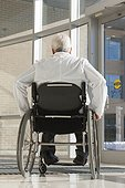 Doctor with muscular dystrophy in wheelchair at hospital entrance
