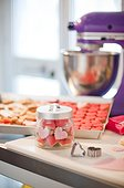 Jar Filled with Heart-Shaped Cookies next to Cookie Cutter and Mixer