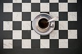 Cup of Coffee and Saucer on Checker Board, High Angle View