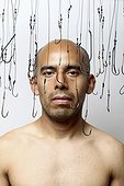 Portrait of Balding Man Surrounded by Hanging Fish Hooks
