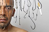 Man Surrounded by Hanging Fish Hooks Looking at Cigarette on Fish Hook, Close-Up